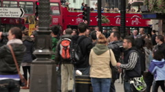 Unidentified people and passing buses on Piccadilly  Stock Footage