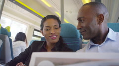 Stock Video Footage of 4k Cheerful businessman and woman discuss newspaper article on commuter train