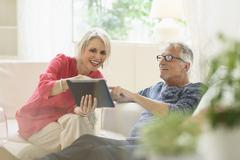 Older Caucasian couple using digital tablet in living room Stock Photos
