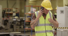 An annoyed businesswoman asks some tough questions to a warehouse manager. - stock footage
