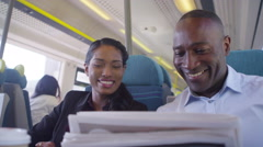 4k Cheerful businessman and woman discuss newspaper article on commuter train Stock Footage