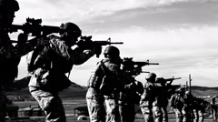 High contrast black and white shot of soldiers practicing firing technique. Stock Footage
