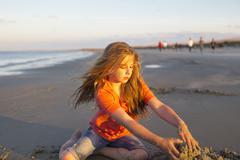 Caucasian girl building sandcastle on beach Stock Photos