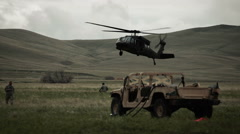 Helicopter landing in field with surrounding Humvee and soldiers - stock footage