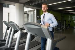 Businessman Running On Treadmill In Gym - stock photo