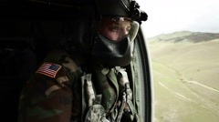Soldier gazing out of helicopter door Stock Footage