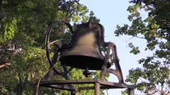 Old church bell in field near trees. Stock Footage