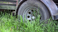 Old trailer wheel in tall grass Stock Footage