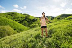 Mixed race athlete standing on rural hillside Stock Photos