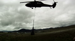 Soldiers point of view from field of Black Hawk helicopter lifting cargo. - stock footage