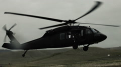 Shot of Black Hawk helicopter landing in field with water droplets hitting lens. - stock footage
