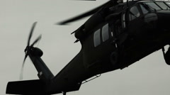 Stock Video Footage of Close up shot of Black Hawk helicopter approaching landing site.