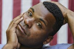 Close up of concerned Black man  in front of American flag Stock Photos