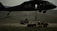 Stock Video Footage of Static shot of Black Hawk helicopter hauling off Humvee.