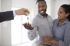 Realtor giving couple keys to new home Stock Photos