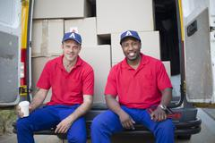 Delivery men sitting with packages in van Stock Photos