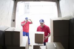 Delivery men unloading packages in van Stock Photos