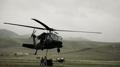 Stock Video Footage of Shot from field of Black Hawk helicopter hauling off cargo.