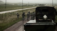 Soldiers and transport vehicles on muddy road. Stock Footage