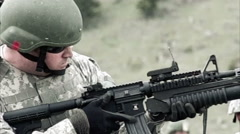 Slow motion clip of soldier learning to use a 40 mm grenade launcher attached to Stock Footage