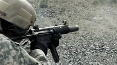 Static shot, soldier shooting automatic small target rifle at range while Stock Footage