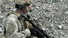 Static shot of soldier shooting automatic small target rifle at range while Stock Footage