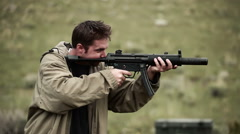 Man in a tan jacket shoots an MP5 Stock Footage