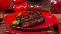 Grilled bbq roast beef steak on red plate with green chili pepper Stock Footage