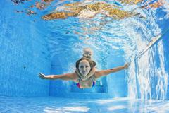 Mother with child swimming and diving underwater in pool - stock photo