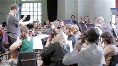 Orchestra rehearsal: string section and conductor Stock Footage