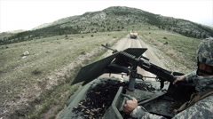 Humvee gunner shoots from top the vehicle - stock footage