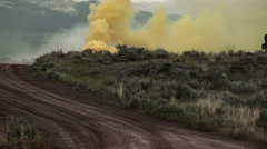 Yellow smoke signal on the side of a dirt road. Stock Footage