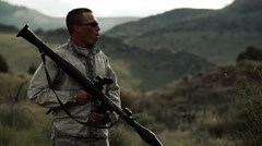 A soldier is holding a rocket propelled grenade launcher and looking around. Stock Footage