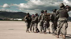 Soldiers lining up and preparing to board a helicopter at an airfield. Stock Footage