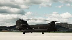 Stock Video Footage of Chinook helicopter at an airfield with rotors spinning.