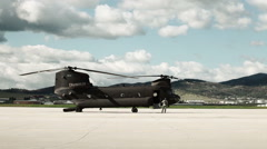 Soldier walking away from a CH-47 Chinook Helicopter as it powers up. - stock footage