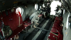 A soldiers come in the back hatch and sit on the red benches. Stock Footage