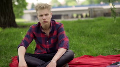 Boy sitting on blanket in the park and doing serious look to the camera Stock Footage