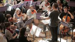 Orchestra rehearsal: conductor and strings - stock footage