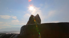 Static shot of water shooting out of the silhouetted rocks of Fly Geyser in Stock Footage