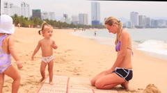 blonde mother and two little girls play on sand beach - stock footage