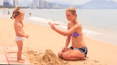 Blonde mother and two little girls build sand castle on beach Stock Footage