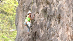 Young woman trying for the first time to rock climb - stock footage