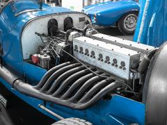 Detail of the engine and exhaust pipes of a vintage racing car. Stock Photos