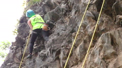 Young woman trying for the first time to rock climb low angle - stock footage