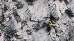 Exhausted rock climber evaluating trajectory on basalt rock Stock Footage