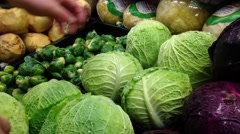 Man selecting savoy cabbage in grocery store Stock Footage