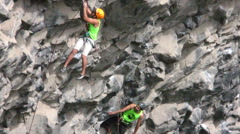Rock climber slowly descending after his performance - stock footage