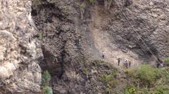Group of unidentified people crossing over Tibetan bridge in Banos de Agua Santa Stock Footage
