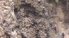 Group of unidentified people crossing over Tibetan bridge in Banos de Agua Santa - stock footage